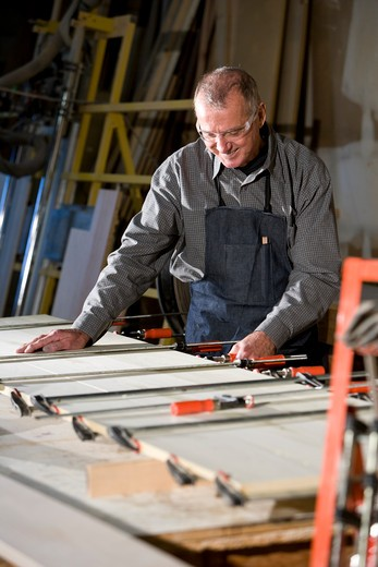 Senior man in woodworking shop working on wood project : Stock Photo
