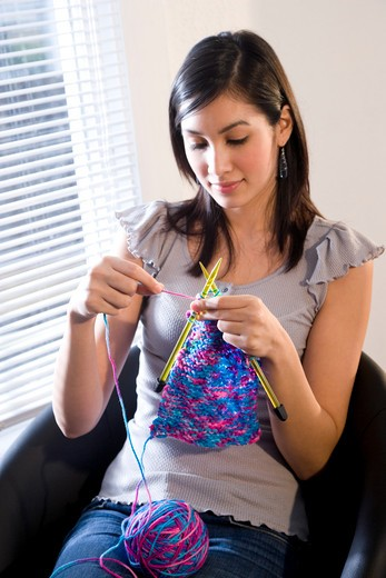 Young woman with yarn and knitting needles : Stock Photo