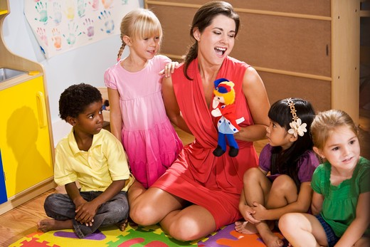 Teacher and preschool children playing with puppet : Stock Photo
