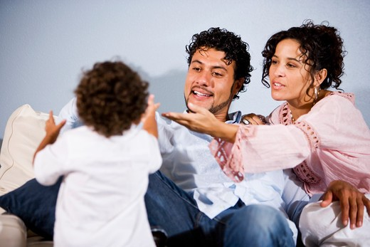 Stock Photo: 1785-41448 Young Hispanic family with one year old son at home in living room