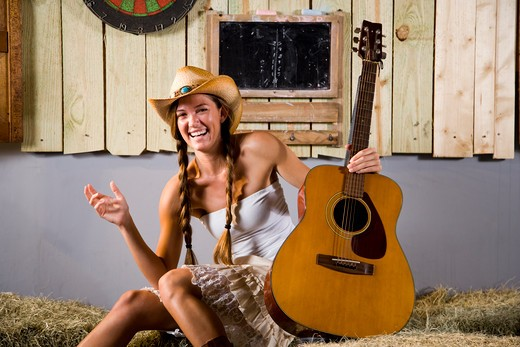 Pretty country western girl with guitar : Stock Photo