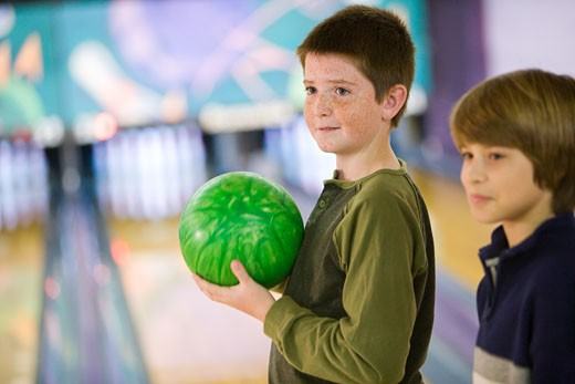 Two pre-teen boys holding bowling ball in bowling alley : Stock Photo