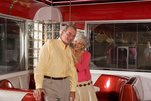 Senior couple standing in old-fashioned diner enjoying themselves : Stock Photo