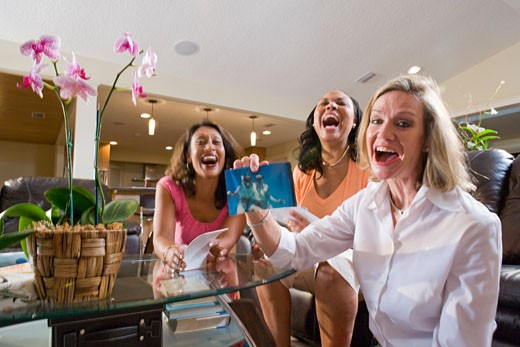 Three happy multi-ethnic women showing photos in living room : Stock Photo