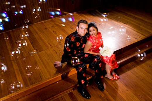 Stock Photo: 1785-8333 Young couple wearing traditional Asian clothing sitting at church altar