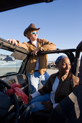 Young interracial couple with jeep at beach : Stock Photo