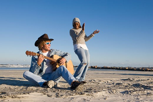 Young interracial couple on beach playing guitar and dancing : Stock Photo