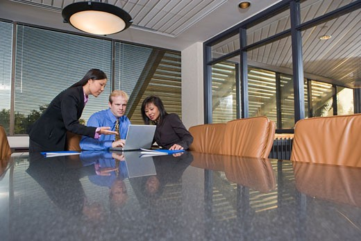 Stock Photo: 1785-8496 Three multi-ethnic businesspeople working on laptop in boardroom