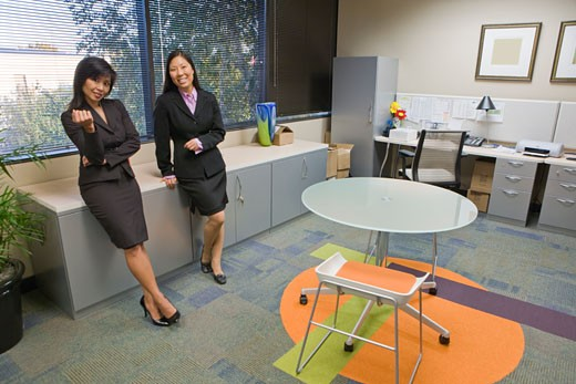 Two female Asian office workers standing in office : Stock Photo