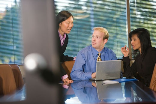 Businesspeople in boardroom working on laptop : Stock Photo