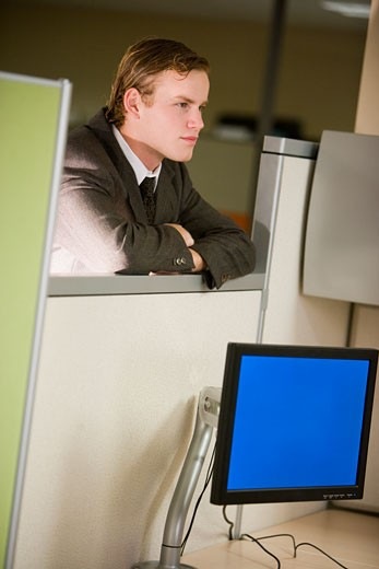 Young male office worker leaning on cubicle wall : Stock Photo