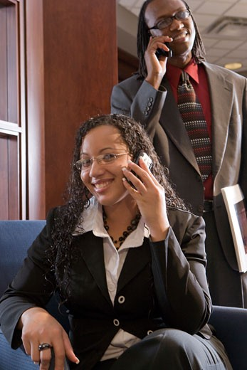 Multi-racial businesspeople using mobile phone in office, focus on woman : Stock Photo