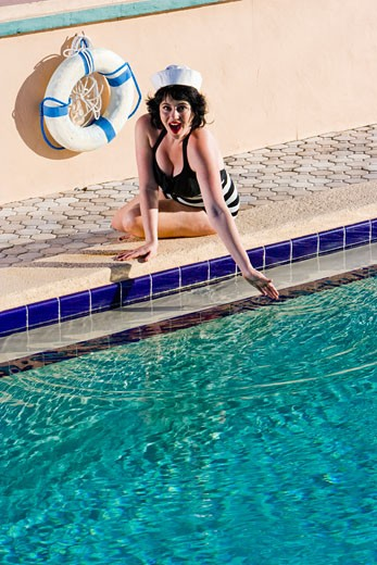 Young woman in sailor hat and bathing suit posed by swimming pool : Stock Photo