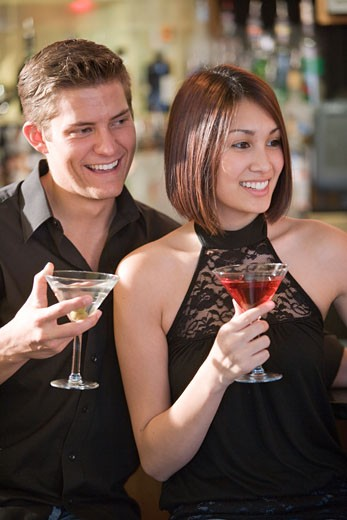 Stock Photo: 1785-9930 Young couple enjoying cocktails together