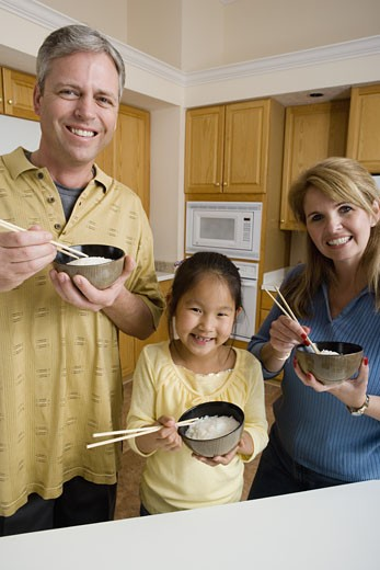 Stock Photo: 1785R-1247 Portrait of a family in kitchen holding bowls of rice and chopsticks