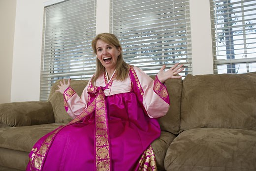 Woman in living room wearing a Hanbok, a traditional Korean costume : Stock Photo