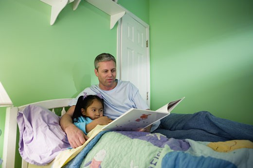 Stock Photo: 1785R-1266 Father with daughter reading book in bedroom