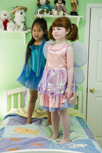 Stock Photo: 1785R-1317 Two young girls in costumes standing on bed