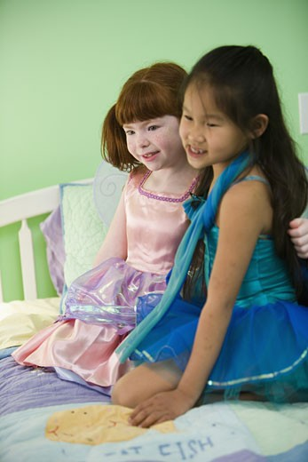 Two young girls in costumes on bed : Stock Photo