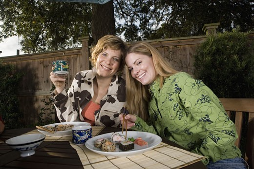 Mother and daughter eating sushi together : Stock Photo