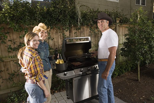 Portrait of a family standing near barbeque grill : Stock Photo