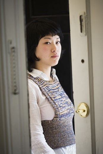 Stock Photo: 1785R-1455 Portrait of a young Asian woman standing at front door