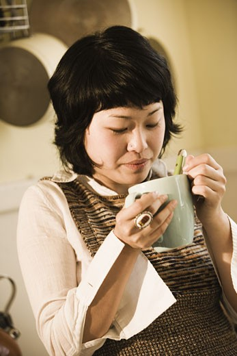 Close-up of young Asian woman drinking from a cup : Stock Photo