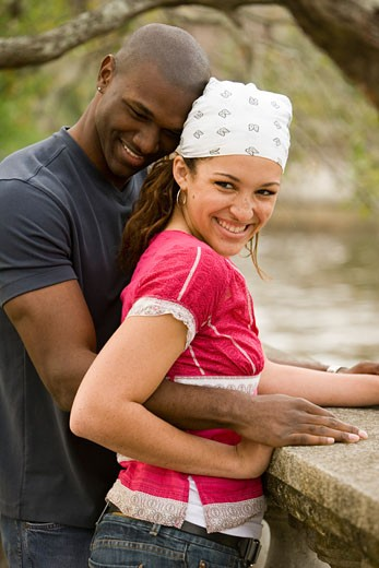 Portrait of a young multi-ethnic couple standing by canal : Stock Photo