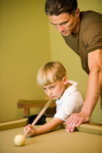 Stock Photo: 1785R-1719 Father showing his young son how to shoot pool
