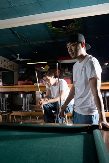Two Asian men in jeans and t-shirts playing billiards : Stock Photo