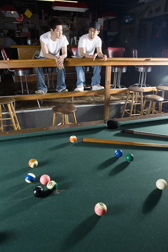Stock Photo: 1785R-1826 Portrait of two men in jeans and t-shirts sitting in front of billiards table