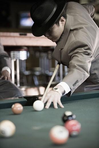 Young Asian man playing billiards : Stock Photo