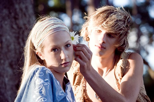 View of a young couple in vintage 1960's hippie, putting flower behind ear : Stock Photo