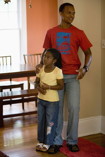 Father and daughter standing inside a house : Stock Photo