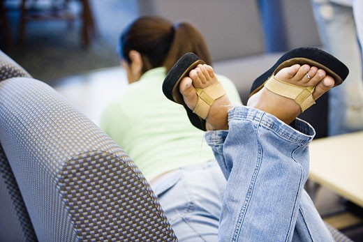 Stock Photo: 1785R-2965 Woman lying on the sofa with feet in the air