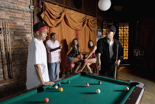Young men in hip-hop fashion shooting billiards : Stock Photo