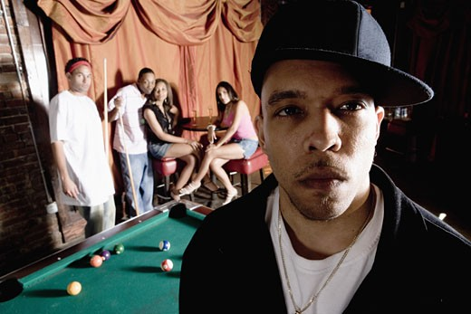 Close-up of a young man in hip-hop fashion with people shooting pool in background : Stock Photo