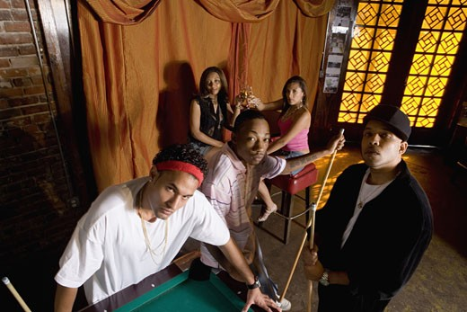 Stock Photo: 1785R-3054 Portrait of young men in hip-hop fashion leaning against pool table
