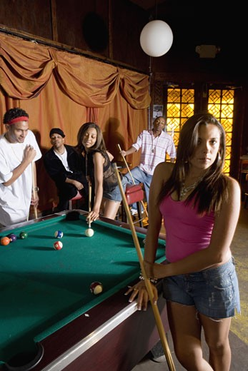 Stock Photo: 1785R-3058 Young woman with pool stick next to pool table with friends watching in background
