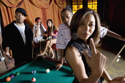 Young woman with pool stick next to pool table with friends watching in background : Stock Photo