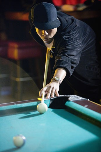 Young man in hip-hop fashion playing pool : Stock Photo