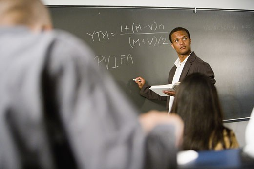 Teacher teaching students in the classroom : Stock Photo