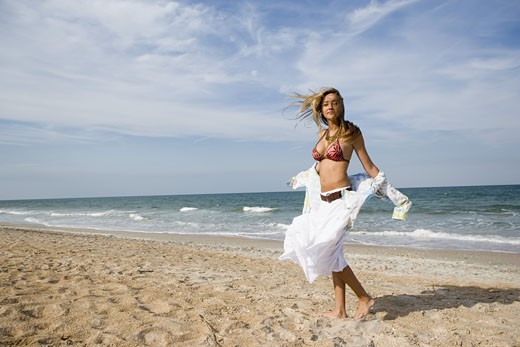 Portrait of a scantily clad young woman standing on a beach : Stock Photo