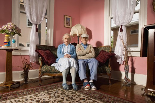 Senior couple sitting on sofa in living room : Stock Photo