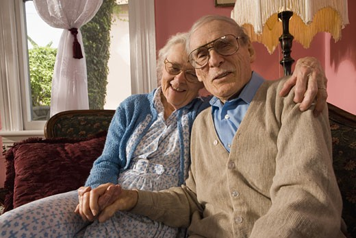 Affectionate senior couple sitting on sofa in living room : Stock Photo