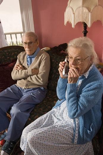 Senior woman talks on cordless phone while grumpy senior man watches : Stock Photo