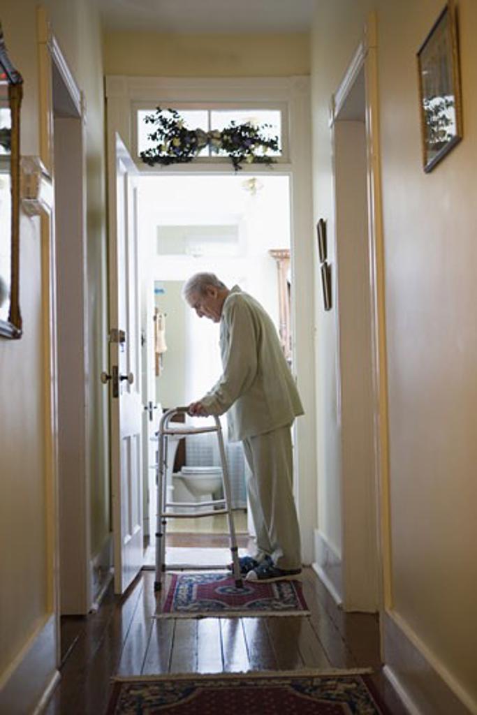 Stock Photo: 1785R-3921 Feeble senior man slowly going down hallway with walker