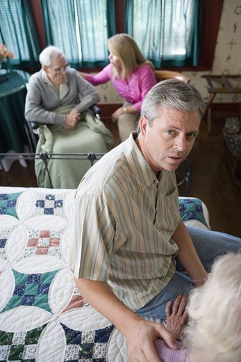Adult children visiting and comforting senior parents in bedroom : Stock Photo