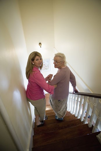 Woman supporting and helping senior woman down the stairs : Stock Photo