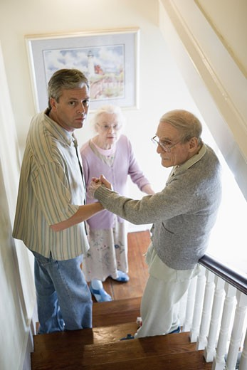 Man helping elderly man down the stairs while senior woman watches downstairs : Stock Photo